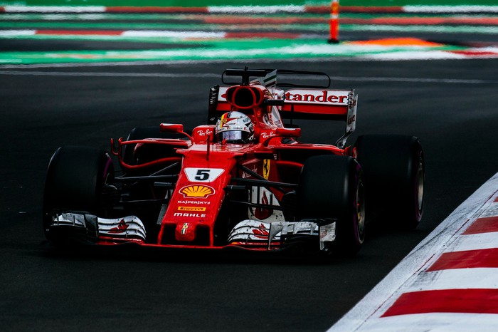 A Ferrari race car driven by Sebastian Vettel is shown at speed on a racetrack.