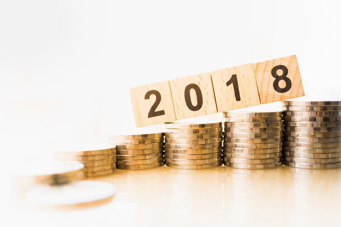 Wooden blocks with 2018 on top of ascending stacks of coins