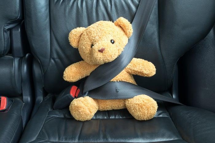 Stuffed bear in carseat with seatbelt around it.