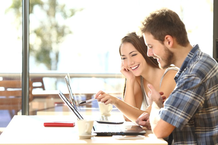 Man and woman pointing at a laptop and smiling