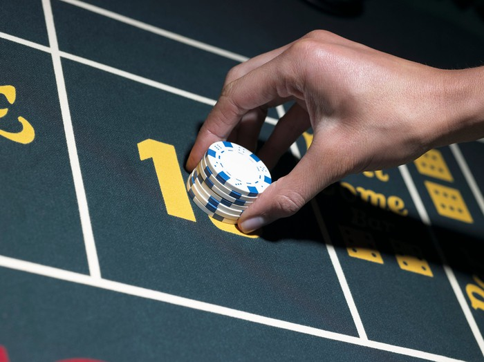 Hand placing gambling chips on a casino table.