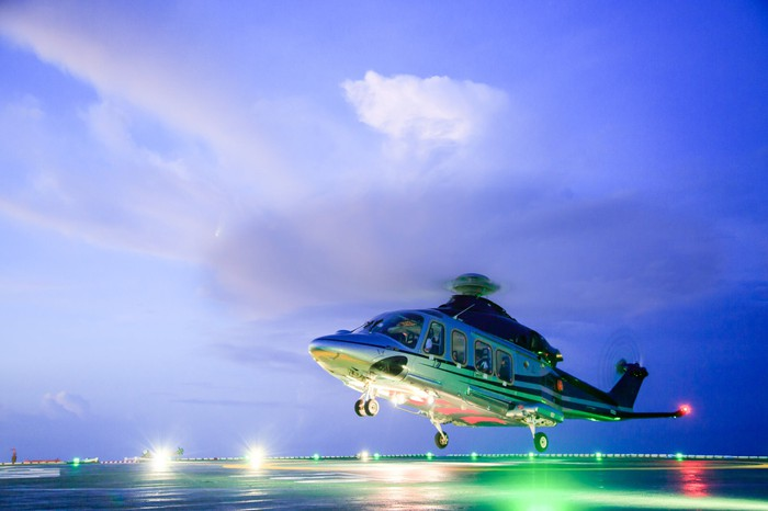 Helicopter landing on a heli pad at dusk.
