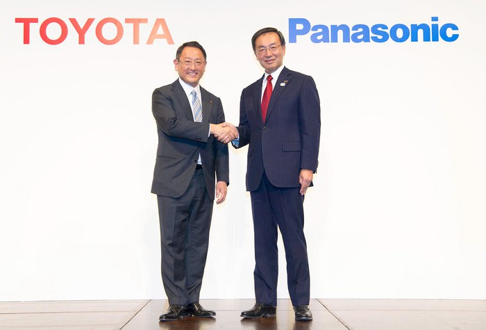 Akio Toyoda and Kazuhiro Tsuga are standing, shaking hands, in front of a backdrop with Toyota and Panasonic corporate logos.