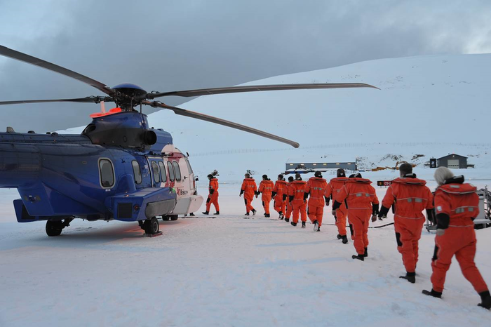 Workers lined up to board a helicopter on an icefield in Stavanger, Norway.