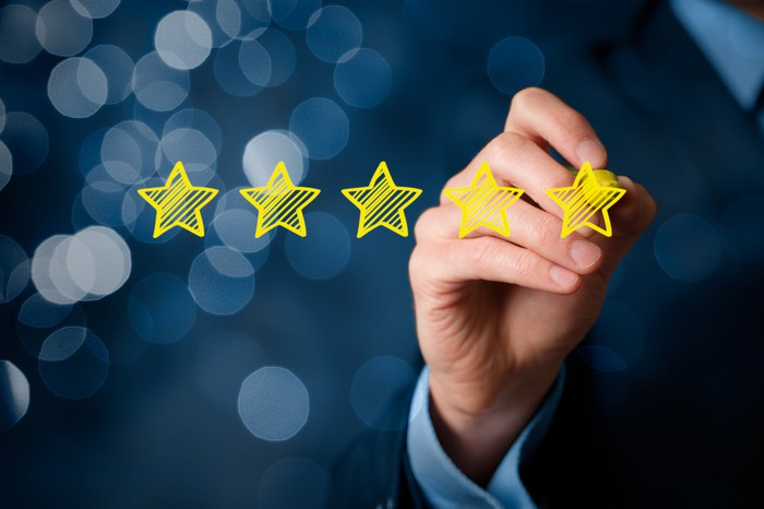 A business person drawing a five-star rating