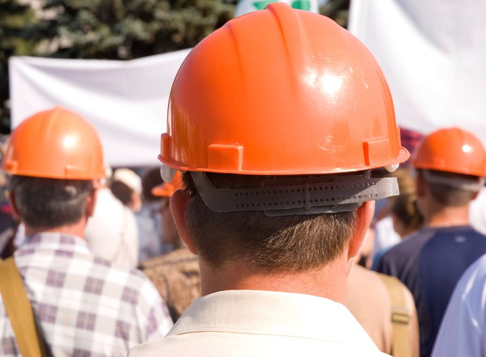Men in hard hats appearing to be on strike.