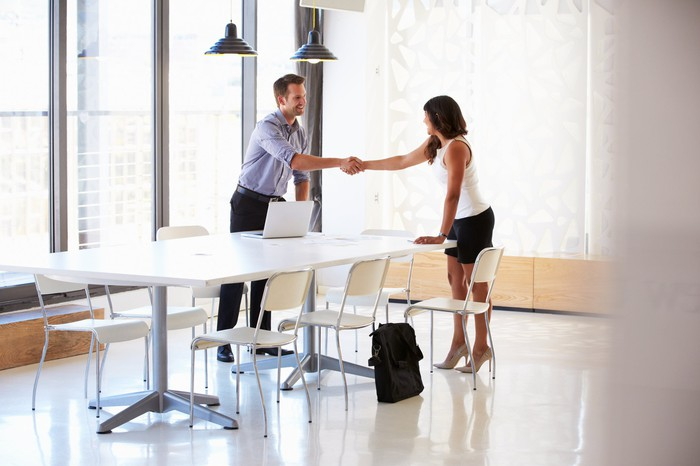 Male and female professional shaking hands across a table