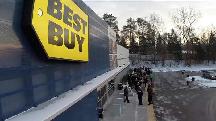 The front of a Best Buy store, with shoppers lined up near the entrance.