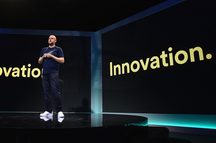 "Spotify CEO Daniel Ek on stage in front of a slide that says ""Innovation."""