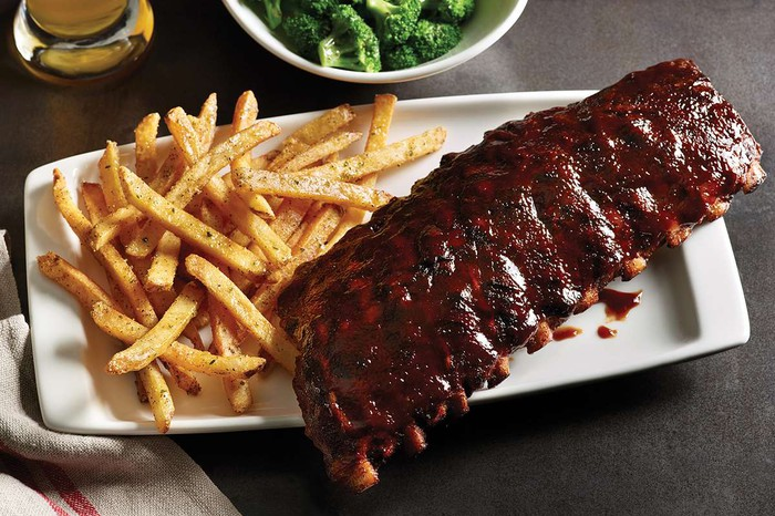 Applebee's ribs with a side of French fries, broccoli, and a beer.