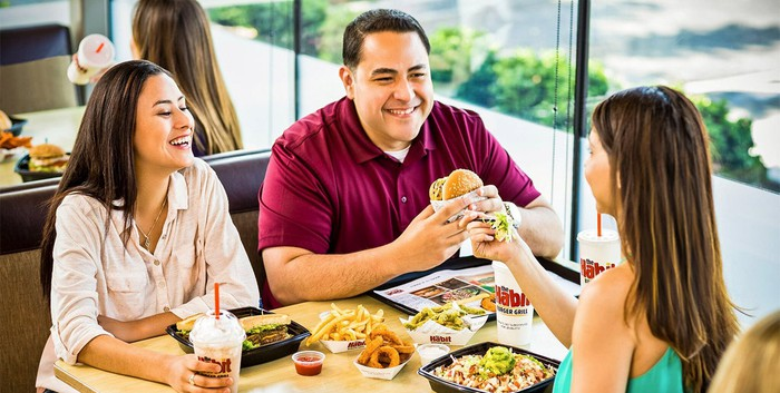 A group of three people sitting beside a window eating burgers and a salad at The Habit.
