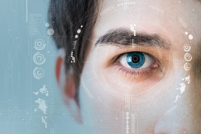 Close-up of a man's eye with technology icons around it.