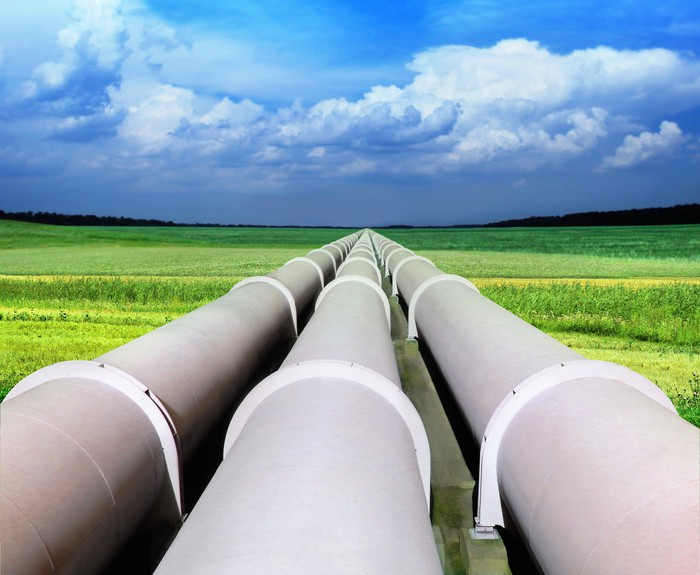 Three pipelines on a green field heading toward the horizon.