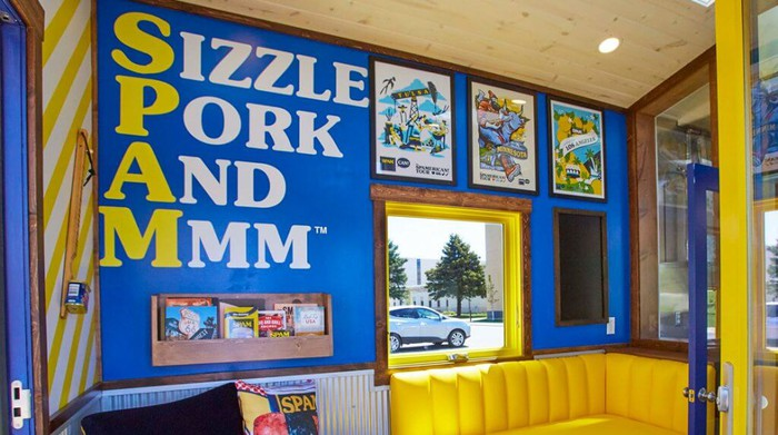 """A wall in a tiny house shows the SPAM acronym """"Sizzle Pork And Mmm"""""""