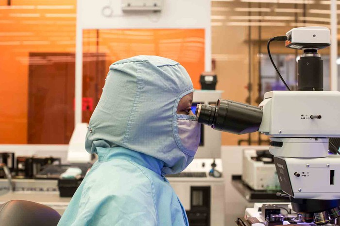 A Finisar employee in a clean suit looking into a microscope