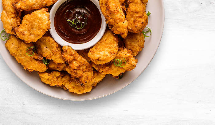 Plate of fried chicken with a dark red-brown sauce in the middle.
