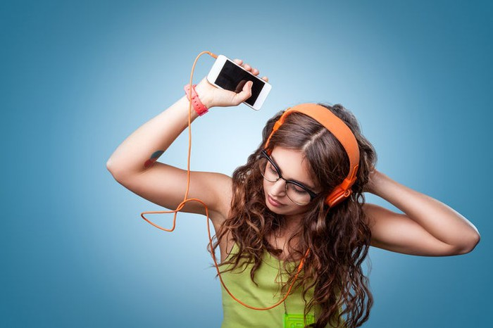 Girl listening to music on her smartphone with headphones and dancing