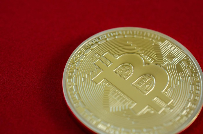 A physical gold bitcoin on a red background.