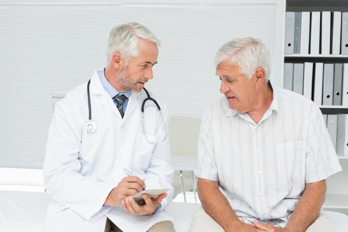 A senior male patient sits next to a doctor who holds a pen and paper in his hands.