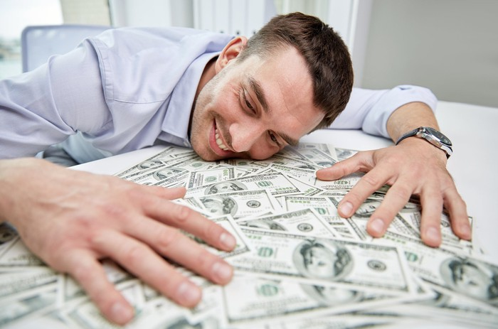 A smiling man resting his head and hands on a pile of cash on his desk.