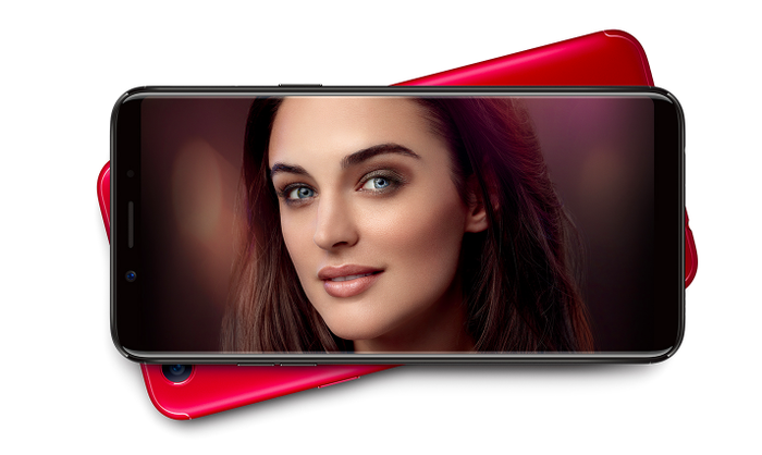 A close up of a black Oppo F5 phone with a picture of a woman's face on the screen.