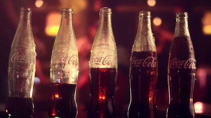 Five Coke bottles with increasing amounts of liquid in them, lined up in a row.