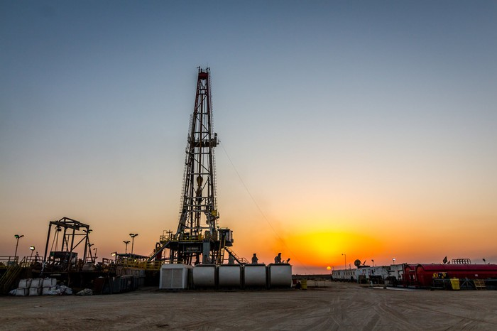A drilling rig with the sun setting in the background.