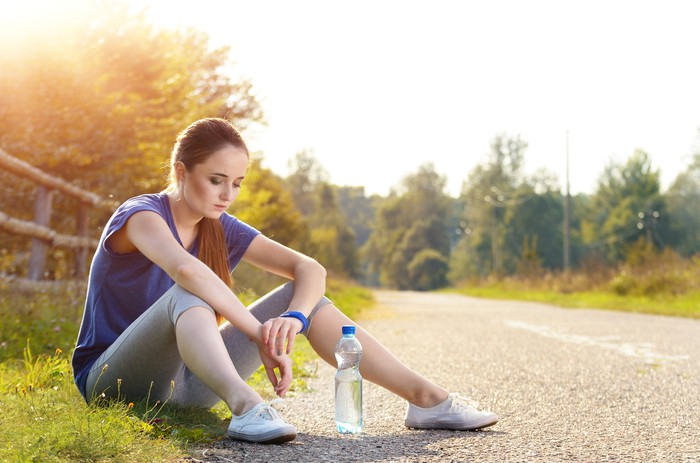 Jogger sitting down, looking glum, wearing a Fitbit