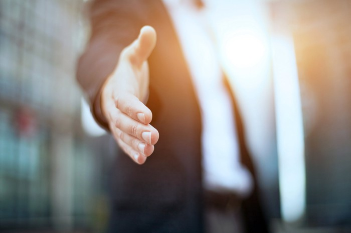 A man in a suit's hand is outstretched to shake another person's hand.