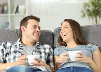 AG couple relaxing with coffee on the couch