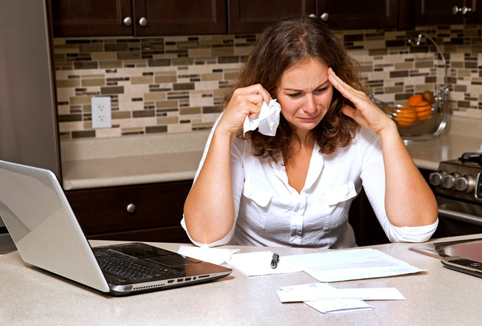 Woman crying while looking at paperwork on top of her kitchen table