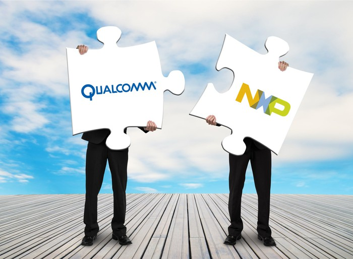 Two men standing on a wooden deck, trying to fit together two large puzzle pieces emblazoned with the Qualcomm and NXP logos.