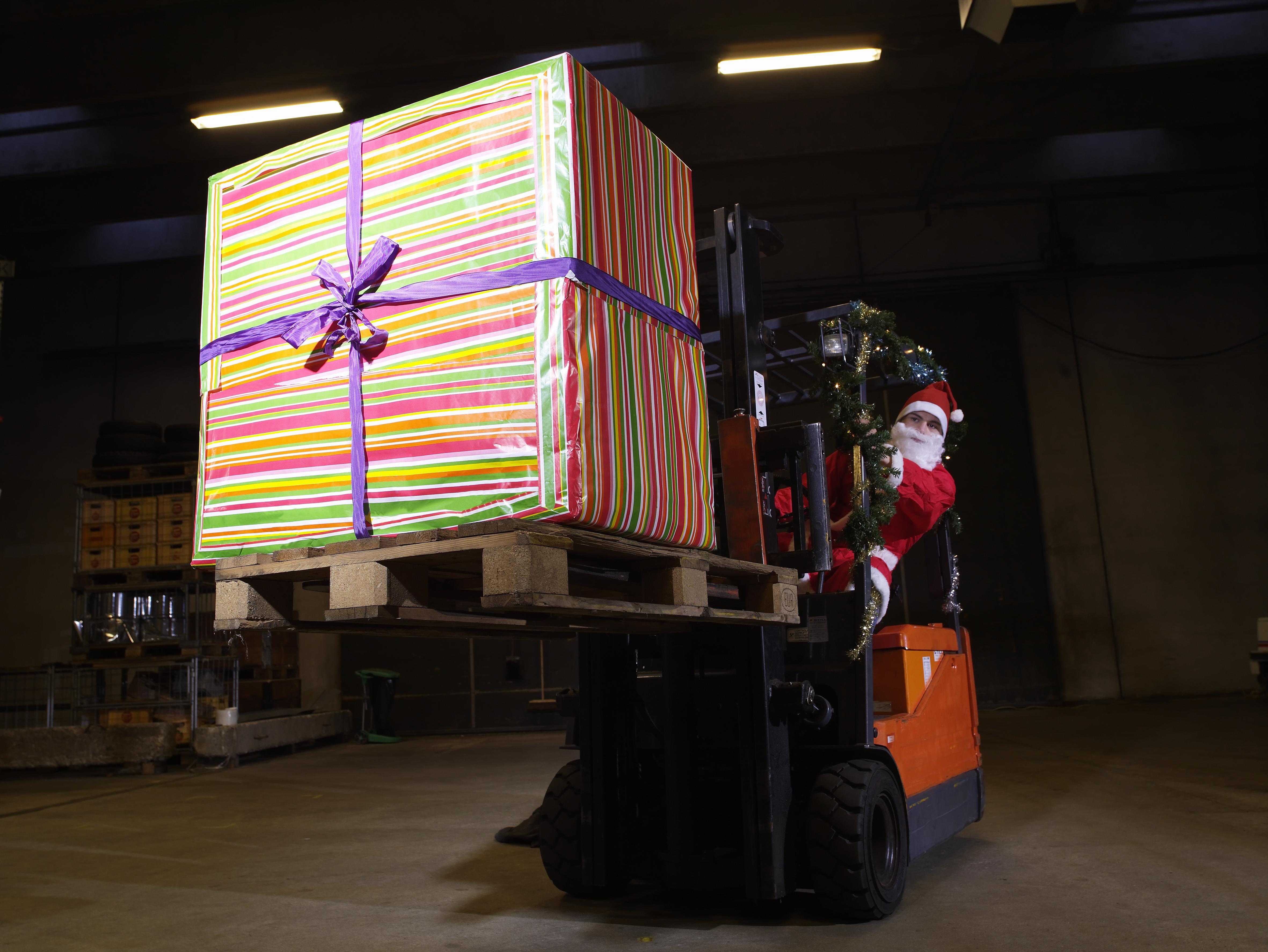 Santa delivering a big present via forklift