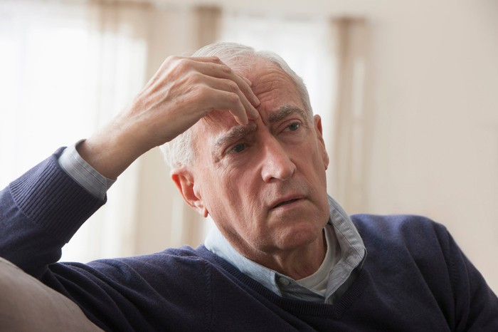 A worried elderly man with his hand on his head.