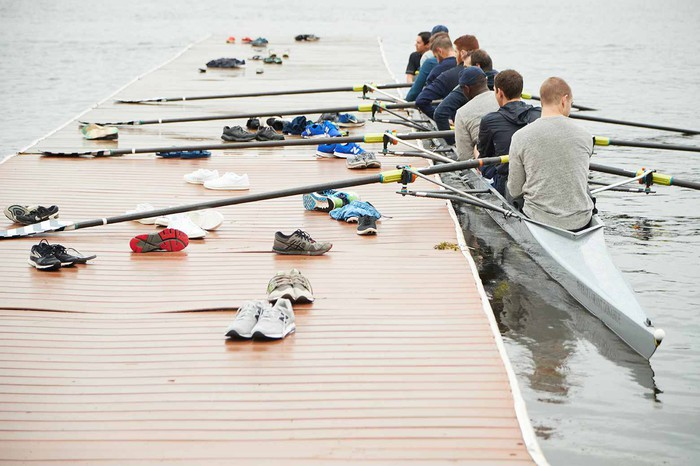 A group of people are in a boat ready to row.