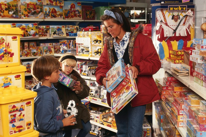 A woman and two children in a toy store.