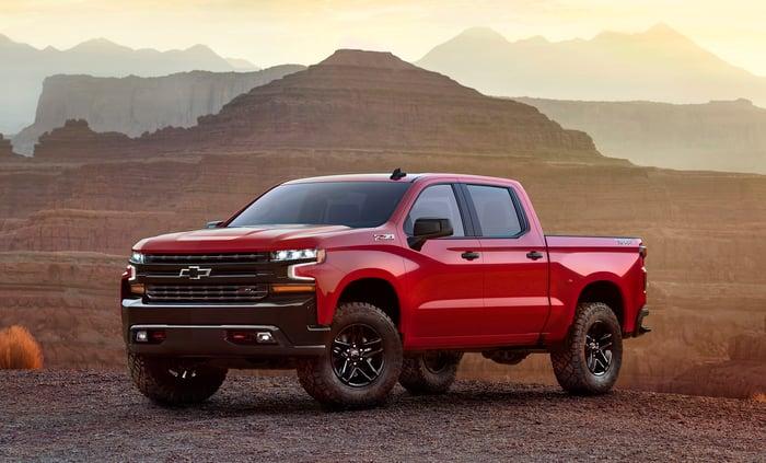 A red 2019 Chevrolet Silverado LT Trailboss, a four-door off-road pickup truck, on rugged desert terrain.