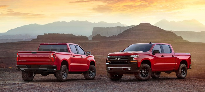 2 red 2019 Chevrolet Silverados, parked to display front and rear details, in a rugged desert setting.