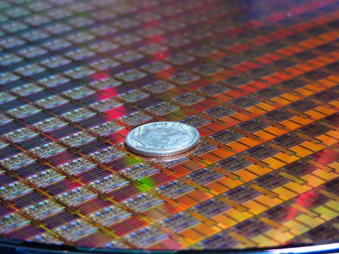 A wafer of Intel processors with a dime on top of it for scale.