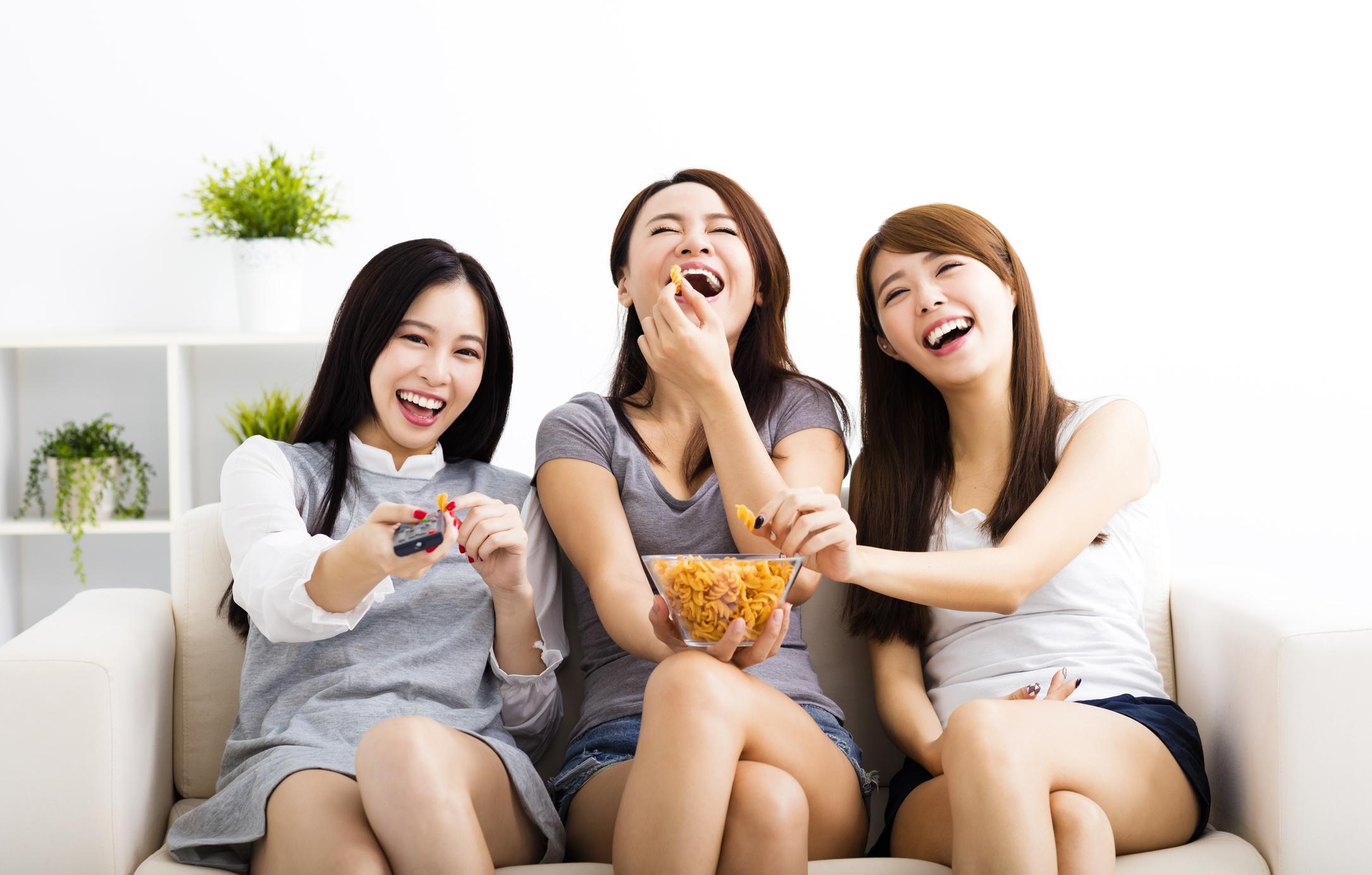 Three young women watch TV.