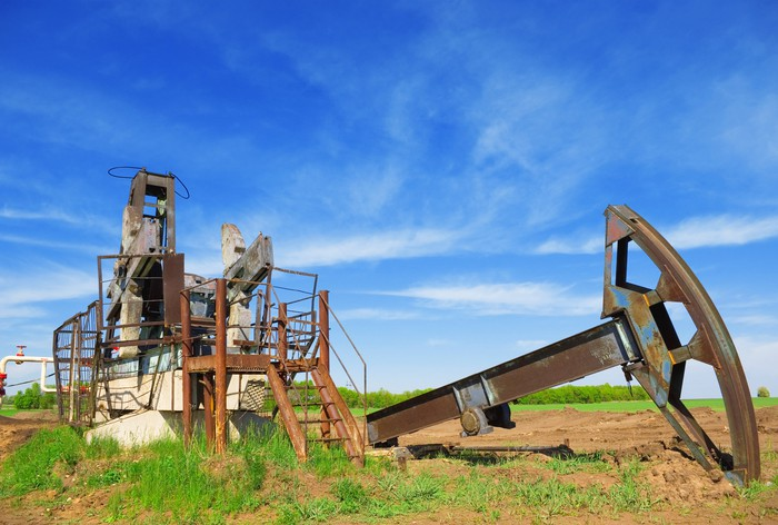 An abandoned oil pump jack in a field.