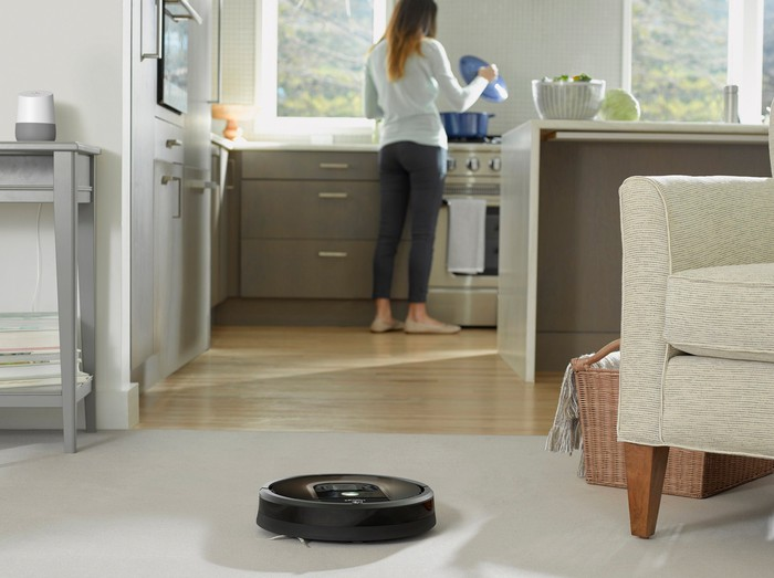 iRobot Roomba 980 vacuum cleaning the floor while a homeowner works in the kitchen