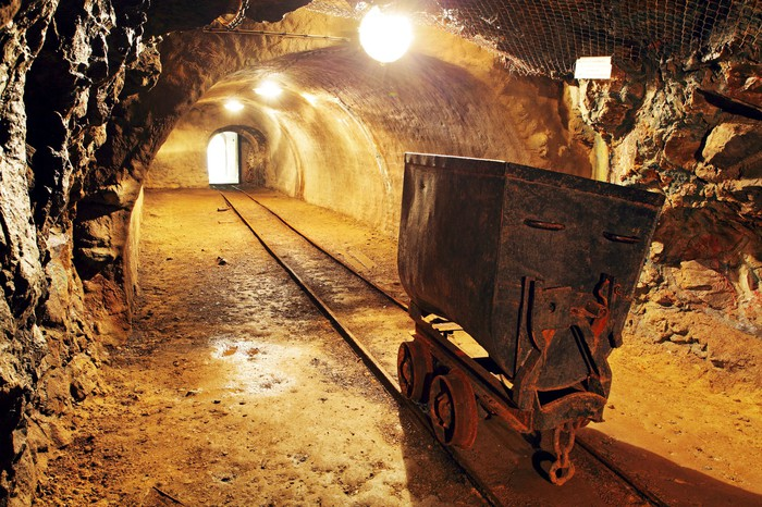 Handtruck on track in a gold mine with exit at end of tracks.