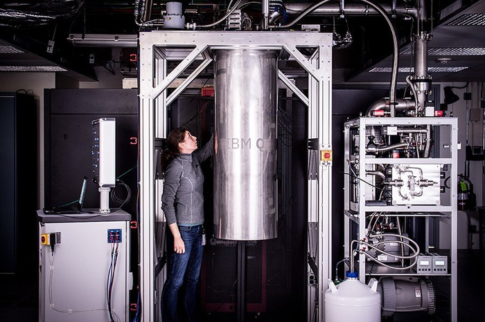A woman standing next to an IBM Q prototype quantum system.