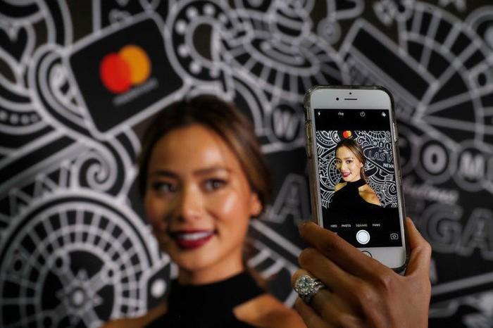 Female taking selfie in front of Mastercard logo and graphic designs on wall.