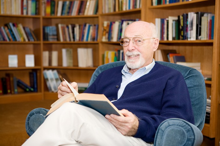 Older man reading a book in a chair