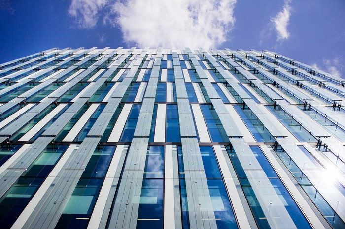 The surface of a glass and metal building with a bright but cloud-filled blue sky above it
