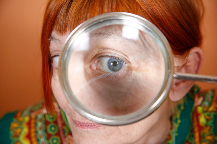 A senior woman looking through a large magnifying glass.