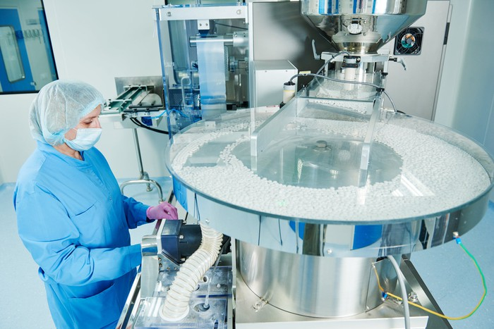 Pharmaceutical worker operates tablet blister packaging machine
