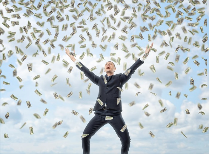 Businessman smiling with hands up surrounded by raining money